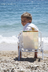 The boy sits in an armchair on a beach
