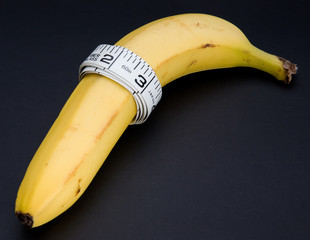 A banana with a tape measure wrapped around it isolated