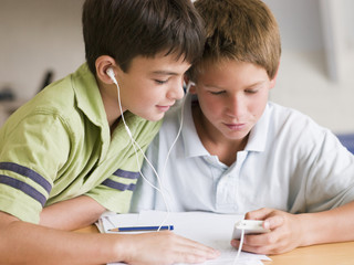 Two Young Boys Distracted From Homework, Playing With MP3