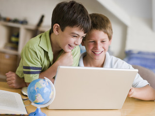 Two Young Boys Using A Laptop At Home