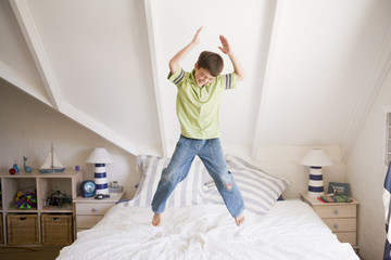Young Boy Jumping On His Bed
