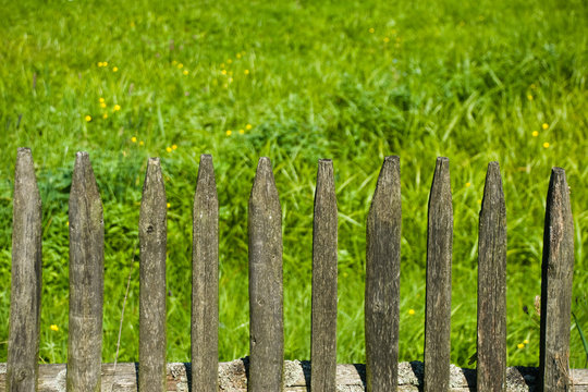 Old wooden fence and a green meadow in a village.