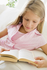 Young Girl Sitting On A Sofa Reading A Book