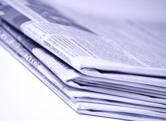 Blue tinted newspapers on light background