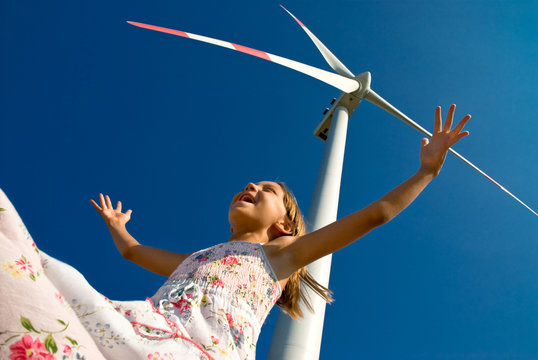 child playing with the wind near a wind turbine