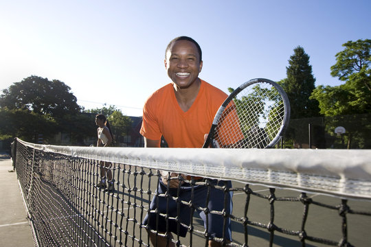 Man playing tennis holding sracket near net.  Horizontal