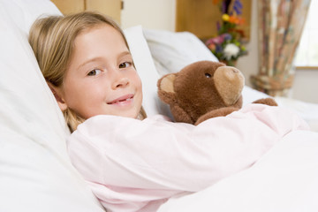 Young Girl Lying In Hospital Bed,Holding Teddy Bear