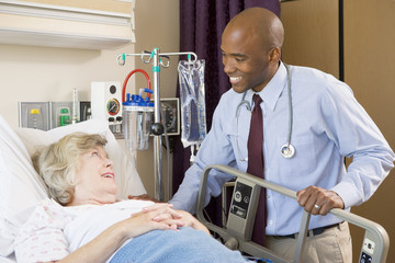 Doctor Talking To Senior Woman Lying In Hospital Bed