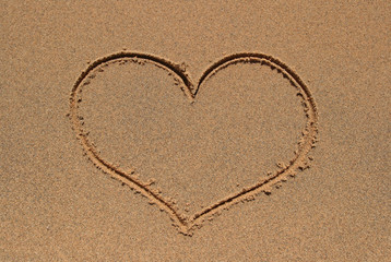 Heart symbol drawn in the sand beach.
