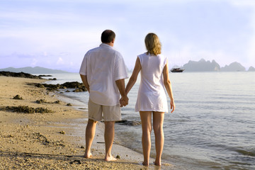A couple walking and holding hands on the beach