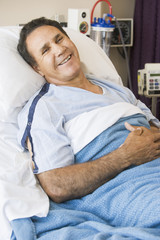 Middle Aged Man Lying In Hospital Bed