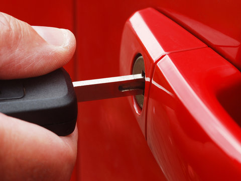 Extreme close-up of man inserting key into car lock