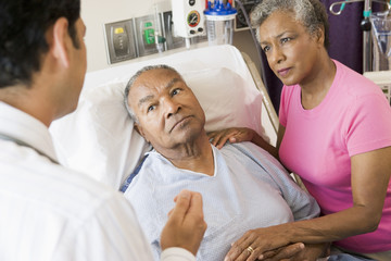 Senior Couple Talking To Doctor,Looking Worried