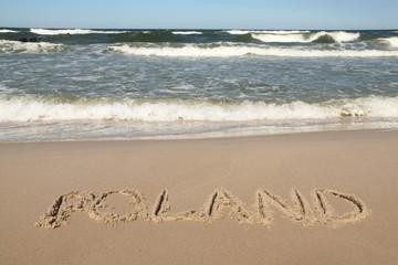 Poland - country name drawn on a sandy beach