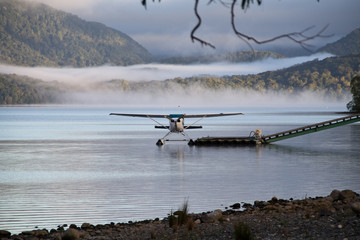 A landed waterplane at the shore - in the foggy hills