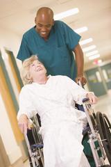 An Orderly Pushing A Senior Woman In A Wheelchair