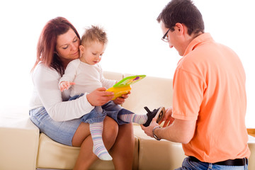 Family of three (father mother and baby boy) sitting on sofa