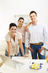 Happy team of office workers running small business,
