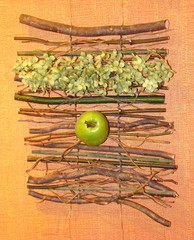 Composition from branches, an apple and green leaves
