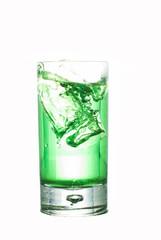 Eiswürfel fällt in ein Glas mit Waldmeistersyrup