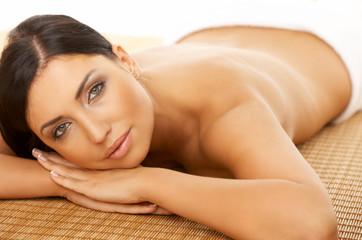 Beautiful brunette woman laying on bamboo mat