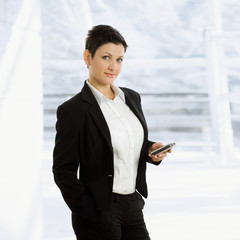 Happy young businesswoman holding mobile phone,