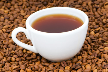 White cup on the background of coffee beans