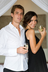 A young couple on honeymoon standing in bedroom with champagne