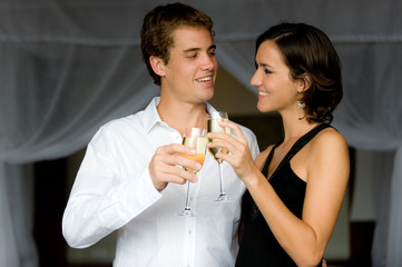 An attractive couple in bedroom with champagne