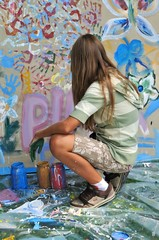 Happy teenager  paint colored wall with yours hand