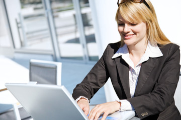 A caucasian businesswoman working on her laptop outdoor