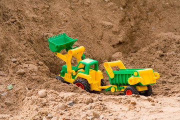 yellow toy bulldozer with the trailer on a heap of sand