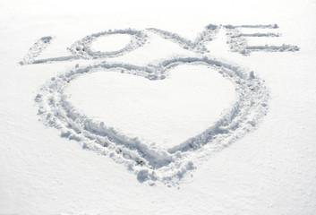 heart and inscription love written on glittering snow
