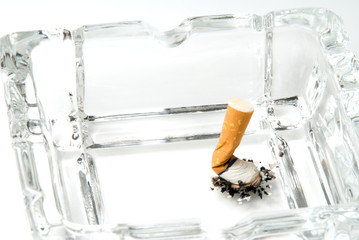 A discarded cigarette butt in an ashtray.