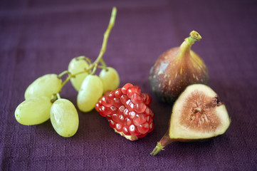 still life of pomgranate, grapes, a whole and slice of fig