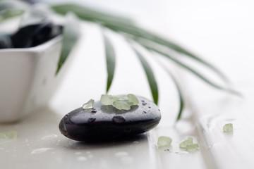 Black massage stones with green bath salt