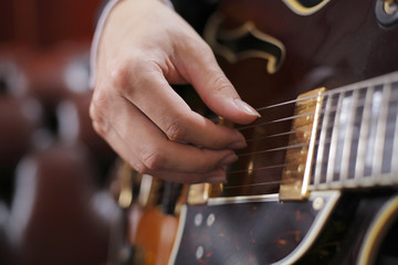 A Hand poicking on guitar strings