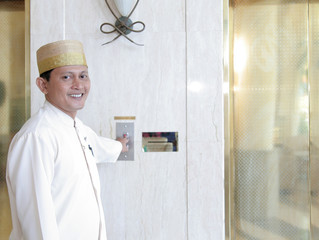 bellboy or bellhop or concierge opening lift for guest smiling