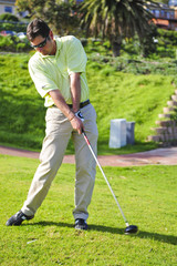 A golfer in action on a practice range, hitting the ball.