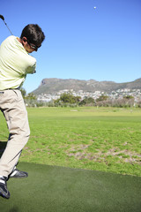 A golfer in action on a practice or driving range.