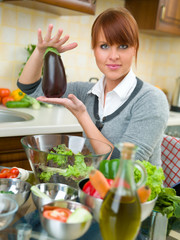 Beautiful woman in kitchen is preparing vegetable salad
