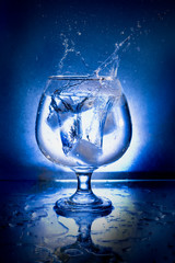 glass and ice on blue background