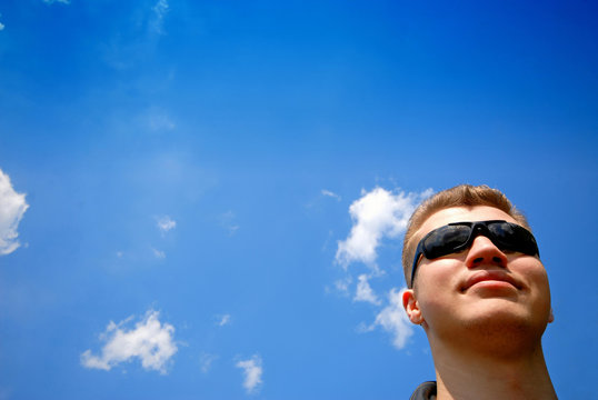 Portrait of  young man in glasses on  background of  blue sky