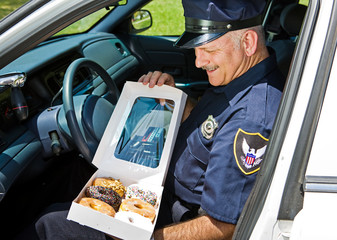 Policeman in his car, hungrily looking at a box of donuts.