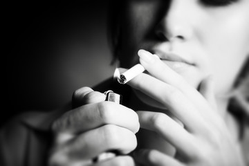 Smoking woman. Focus on cigarette lighter.