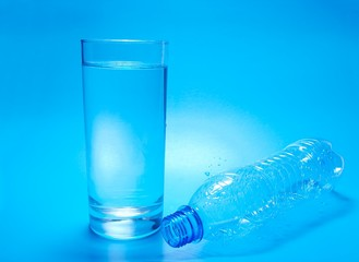 A glass of water and empty bottle on blue background