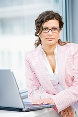Young attractive business woman working on laptop