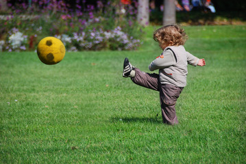 a baby playing football