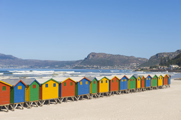 Brightly colored dressing huts on the beach.