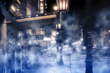 foggy street scene with lights and peolpe at night
